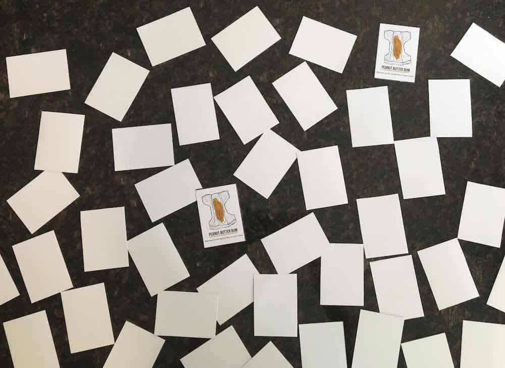 A photograph of 46 printable playing cards arranged randomly and face down on a granite counter top. Two matching cards are face-up, showing cards with illustrations of baby poop in a diaper.