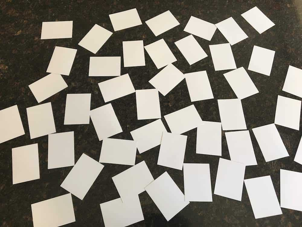 A photograph of 46 blank white printable playing cards arranged randomly and face down on a granite counter top.