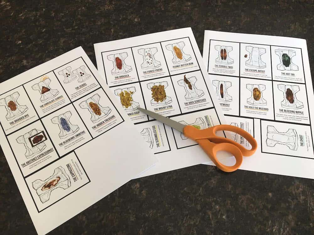 A photograph of a set of print at home cards that are part of a free printable baby shower game. The cards feature illustrations of different baby poop in diapers.