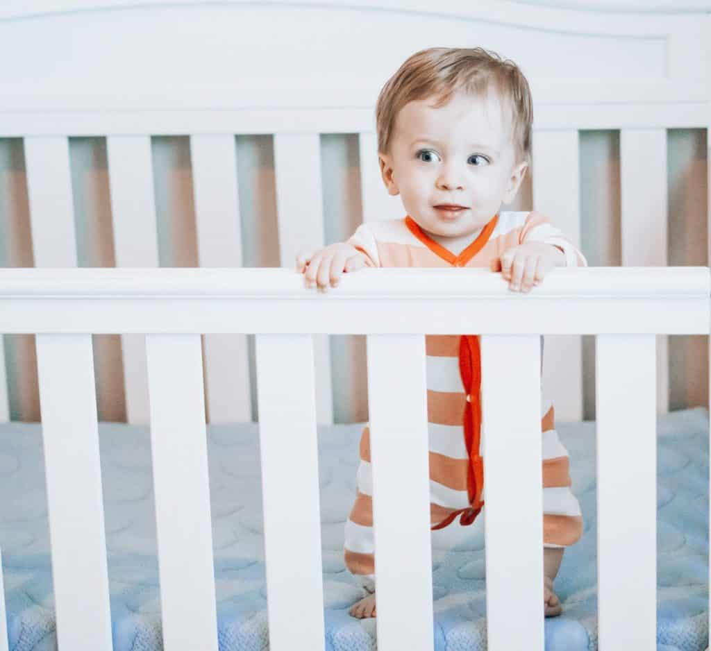 The Nook Pebble mattress in a white crib with a baby boy dressed in orange and white pyjamas standing on the mattress against the crib rail