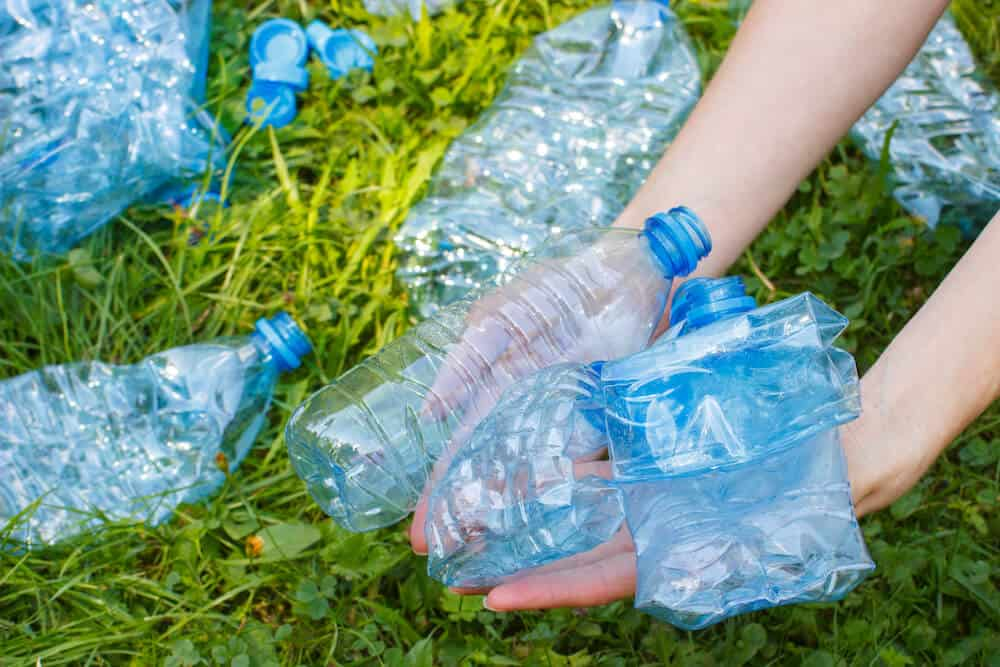 Empty Polyethylene Terephthalate (PETE or PET) water bottles in the hand of someone cleaning litter from a patch of grass.