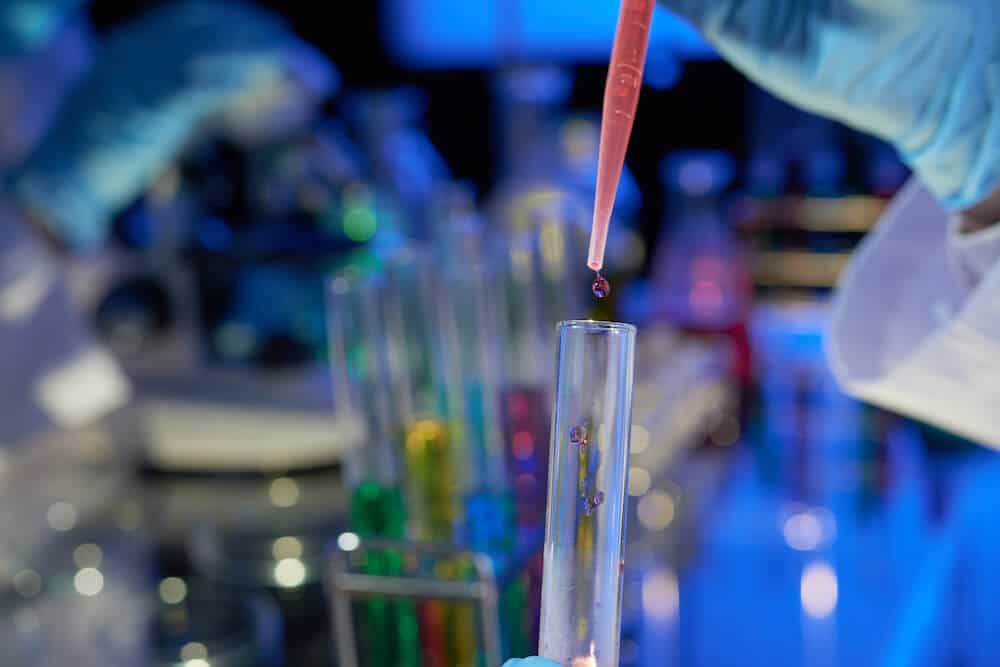 a close up view of liquids being dropped into a test tube in a lab