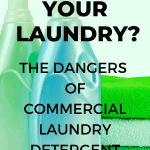 A Pinterest pin image featuring a photograph of a baby in a bath towel. There is text on the image that says Toxins in Your Laundry? The Dangers of Commercial Laundry Detergent