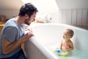 father and toddler at bath time. A bath spout cover is an essential part of bath time for your child's safety