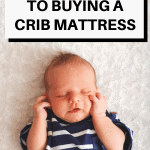 A Pinterest pin image featuring a photograph of a baby sleeping in a crib. There is text on the image that says Ultimate Guide to Buying a Crib Mattress.