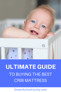 A Pinterest pin image featuring a photograph of a smiling baby in a crib. There is text on the image that says Ultimate Guide to Buying the Best Crib Mattress.