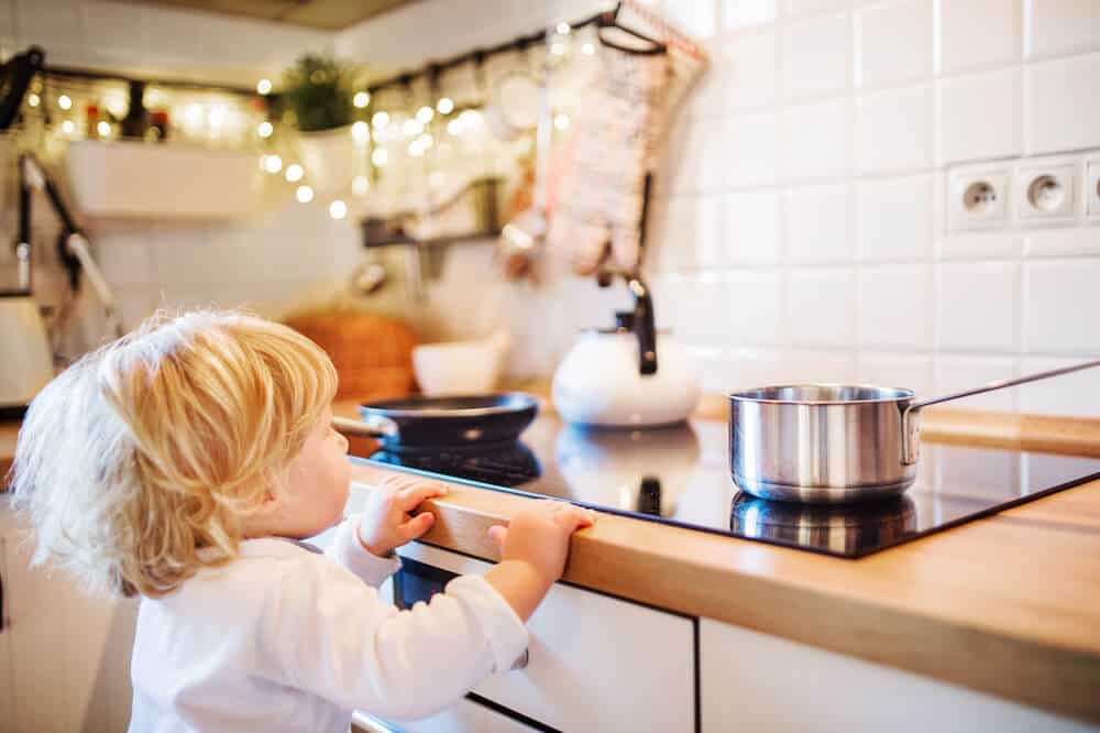 A toddler boy reaches for a hot pot on a stove. Leaving pot handles facing out is a common child proofing mistake.
