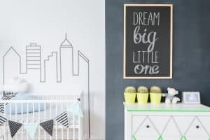 A baby nursery with the top of a crib and dresser in view, along with city themed decorations. The image accompanies an article about the best cribs with storage underneath.