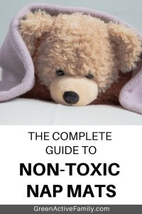 A Pinterest image to accompany and article about the best toddler nap mat. The text says The Complete Guide to Non Toxic Nap Mats. The image shows a teddy bear under a blanket.