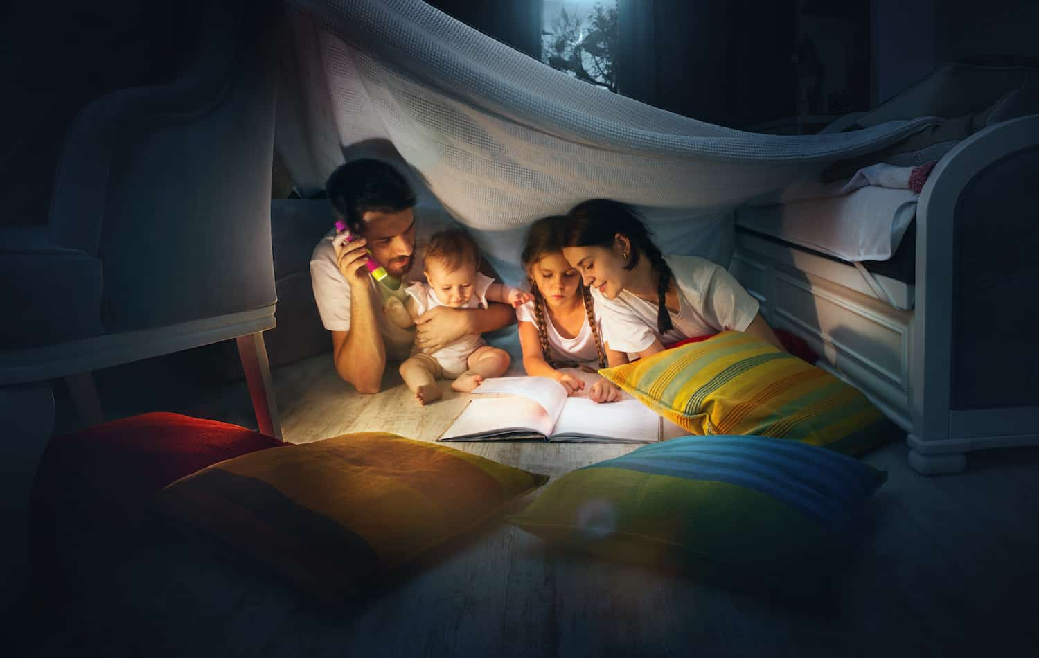 A father reads a book to his children under a play tent in an article about the Best Baby Books for the First Year