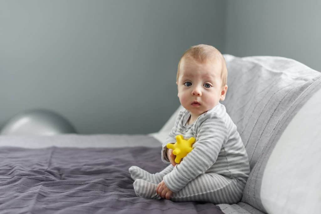 A young baby boy sits on a grey blanket while holding a yellow baby toy. The image accompanies an article about the best baby toys