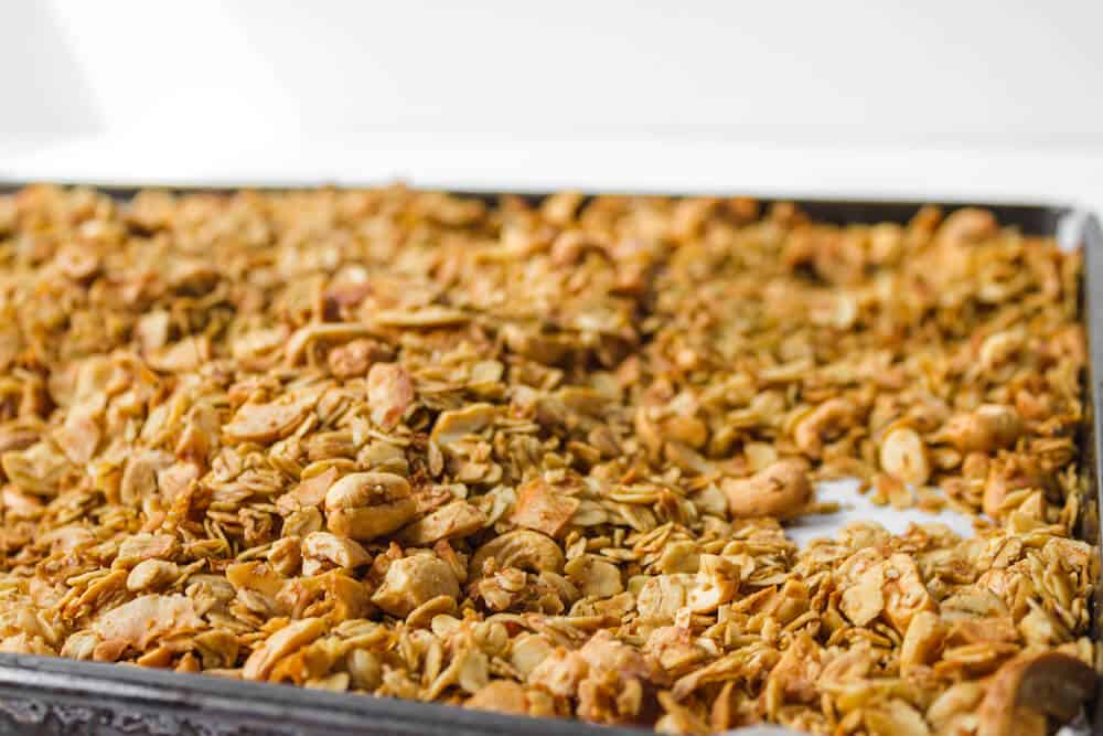 Ingredients for cashew coconut granola spread out on a baking sheet after being toasted
