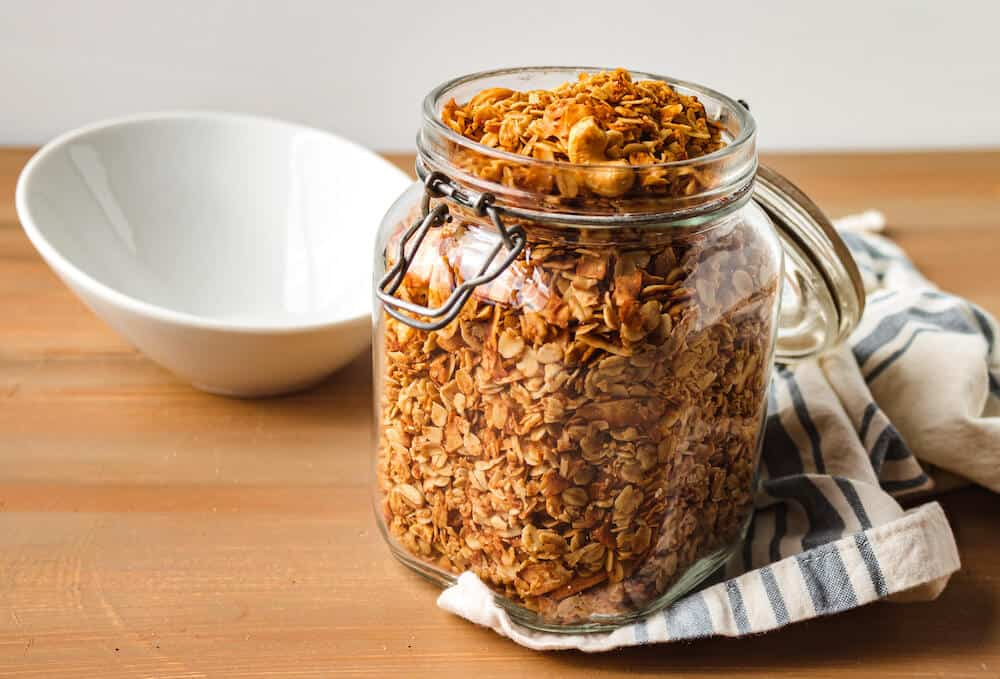 Homemade cashew coconut granola in a storage jar sitting on a wooden table
