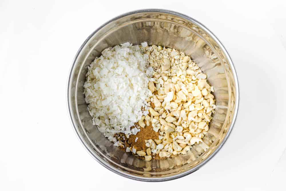 Ground ginger, rolled oats, coconut flakes, and cashews in a stainless steel mixing bowl