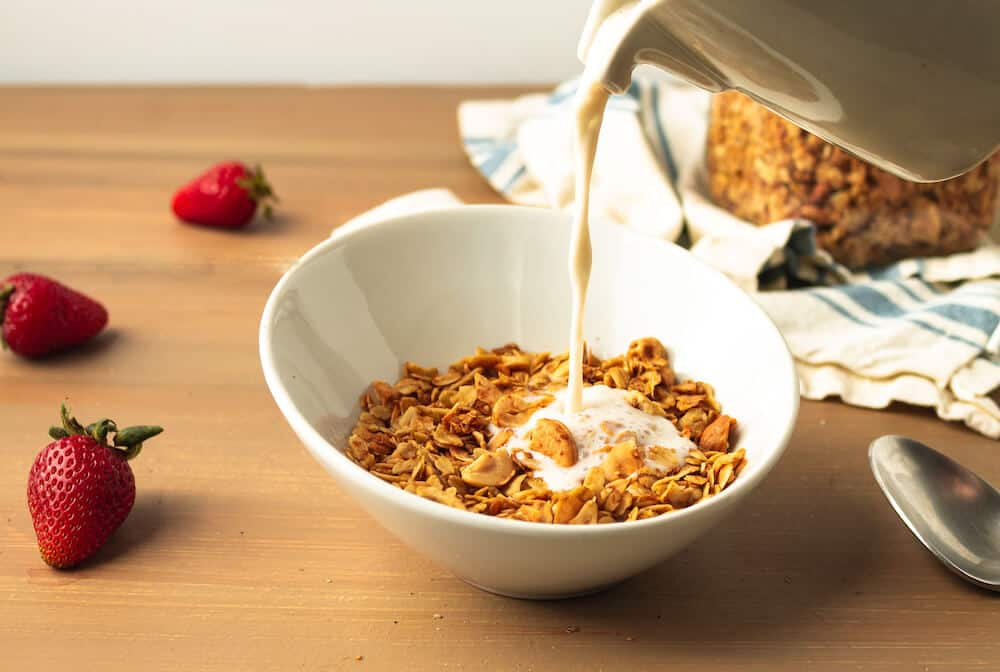 Almond milk being poured from a white ceramic jug into a bowl of coconut cashew granola.