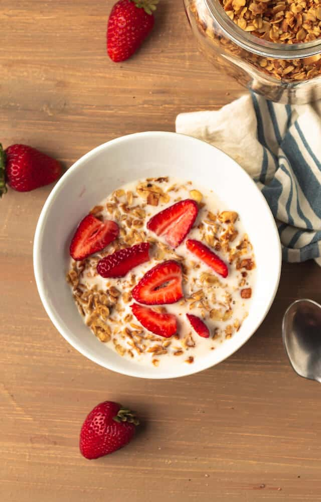 A bowl of cashew coconut granola with plant-based milk and fresh cut strawberries in a white cereal bowl