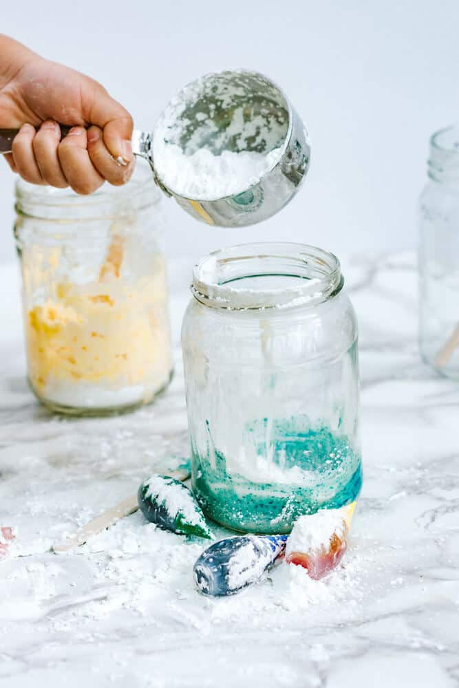 A photograph showing a hand using a metal measuring cup with corn starch in it to mix more corn starch into blue homemade playdough in a glass jar.