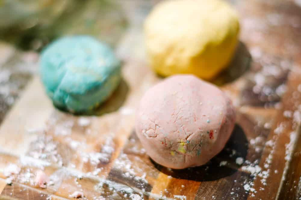 3 homemade playdough balls are arranged on a wooden table covered in cornstarch. The balls are colored pink, yellow and blue. The photo is part of an easy playdough recipe for 2 ingredient playdough