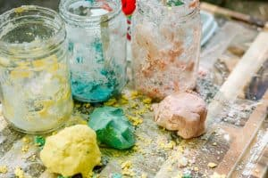3 homemade playdough balls are shown on a wooden table covered in cornstarch. The balls are colored pink, yellow and blue. They look as though they have been nkneeded but not shaped fully. The photo is part of an easy playdough recipe for 2 ingredient playdough