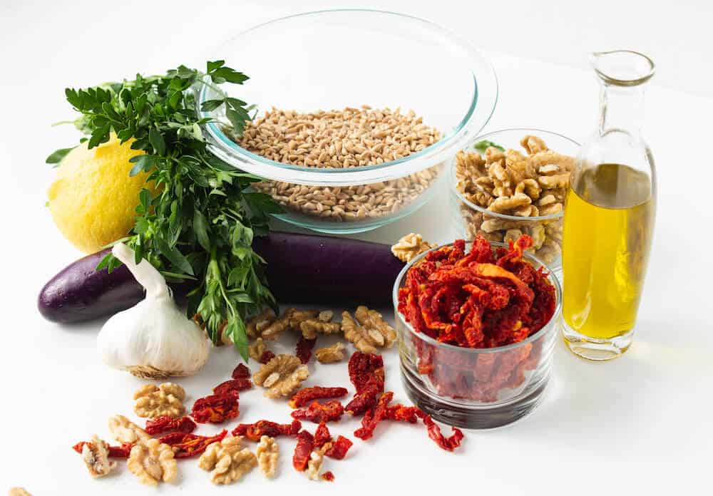 Ingredients for a vegan side dish of farro with sun-dried tomato pesto and eggplant. Ingredients pictured include cilantro, garlic, eggplant, walnuts, sun-dried tomato, farro and olive oil