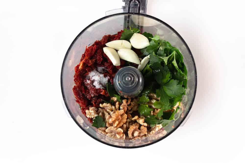 Ingredients for a vegan side dish of farro with sun-dried tomato pesto and eggplant in a food processor.