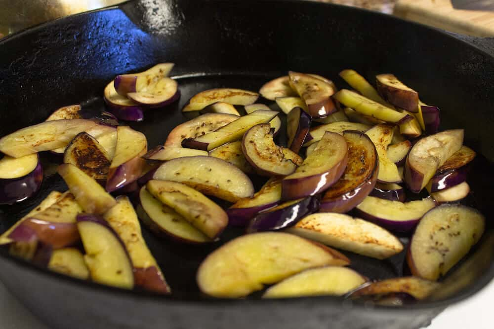Cooking eggplant in a cast iron frying pan as part of a recipe for sun-dried tomato pesto with walnuts.
