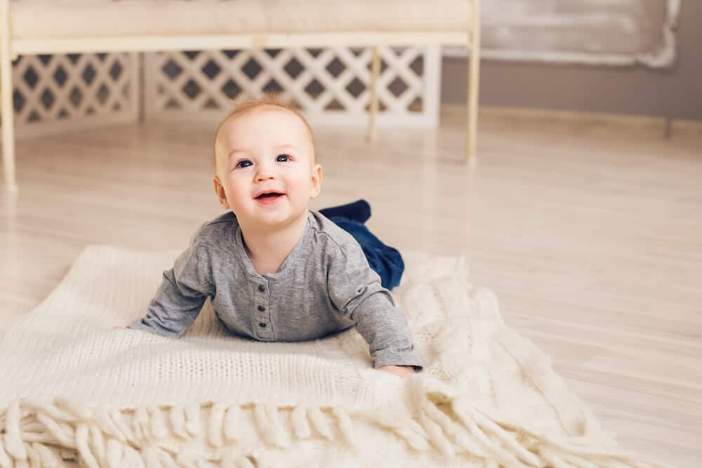 a baby boy doing tummy time on a tummy time mat on the floor. He is pushing up wearing a grey shirt and jeans.