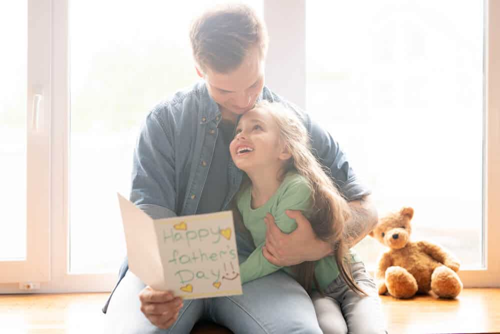 A father has his arm around his daughter as he reads a father's day card she gave to him