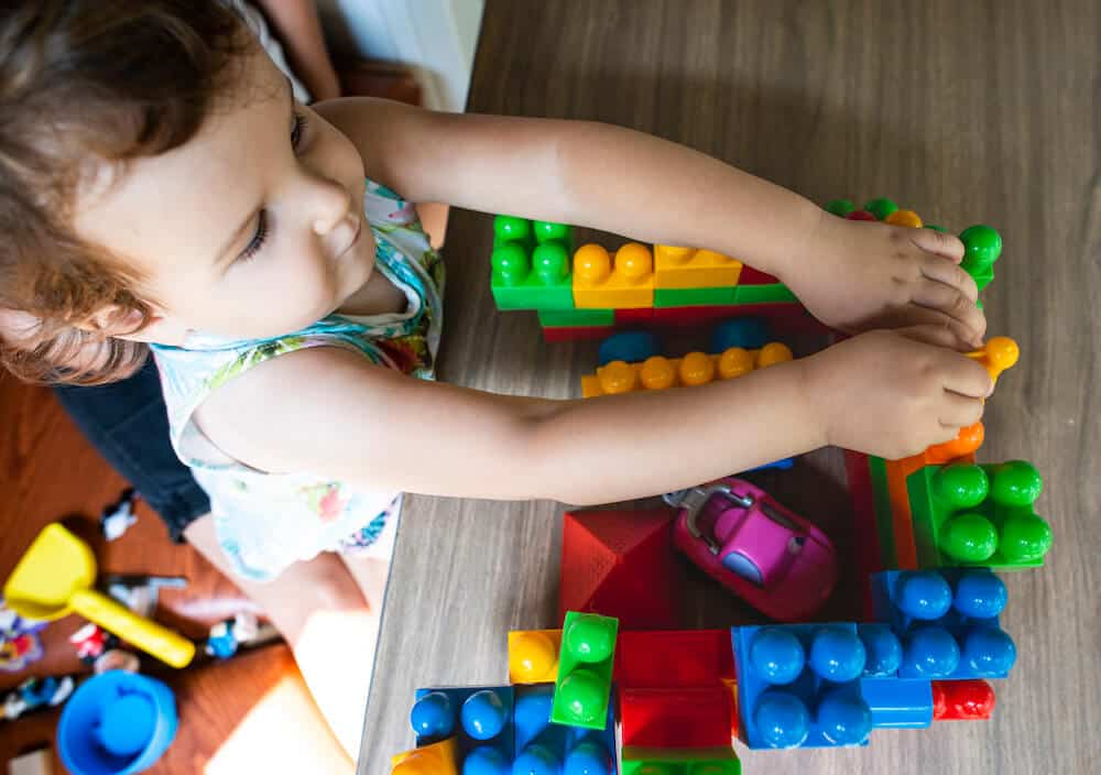 A little girl playing with multi colored plastic blocks on a table.