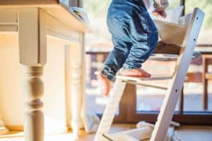 A toddler boy climbing up on a learning tower inside a home.