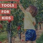 A Pinterest Pin with a toddler reaching for apples off the tree in an orchard. The Text says Garden Tools for Kids