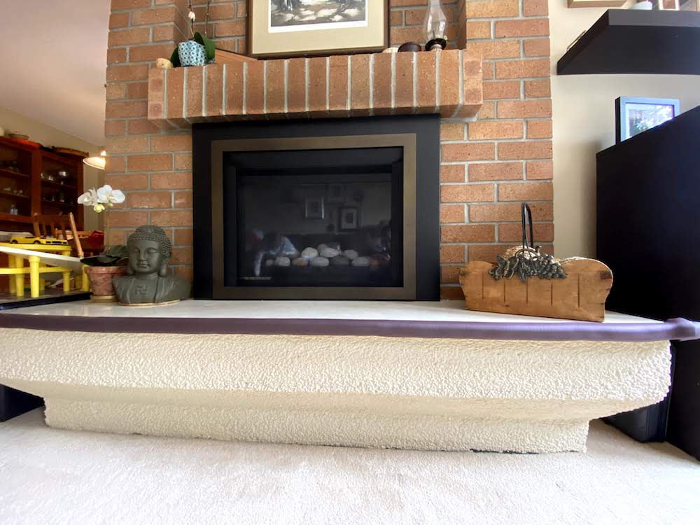 A fireplace with a marble hearth is childproofed using high density brown foam attached to the edges.