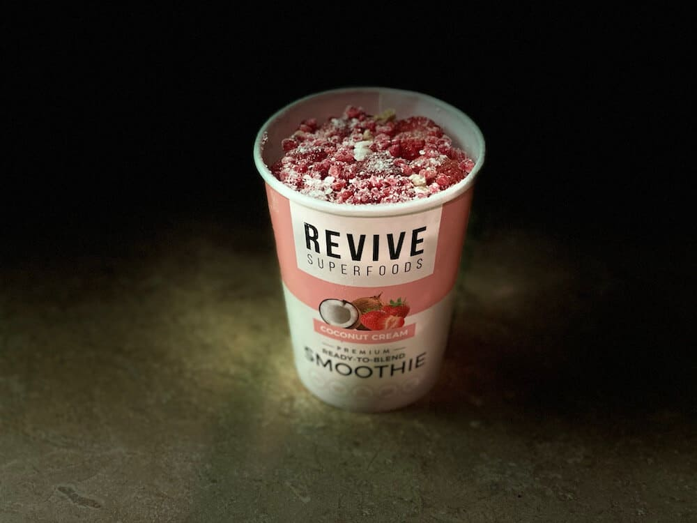 An image of a Revive Superfoods Coconut Cream smoothie  cup on a kitchen counter. The lid is off and the frozen contents of the smoothie cup are visible.
