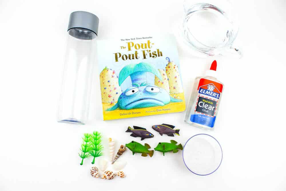 A shot of the materials used to make an ocean sensory bottle for children. The materials include plastic fish toys, plastic aquarium plants, sea shells, glue, water, and a clear plastic bottle against an isolated white background. Also pictured is the children's book, The Pout Pout Fish