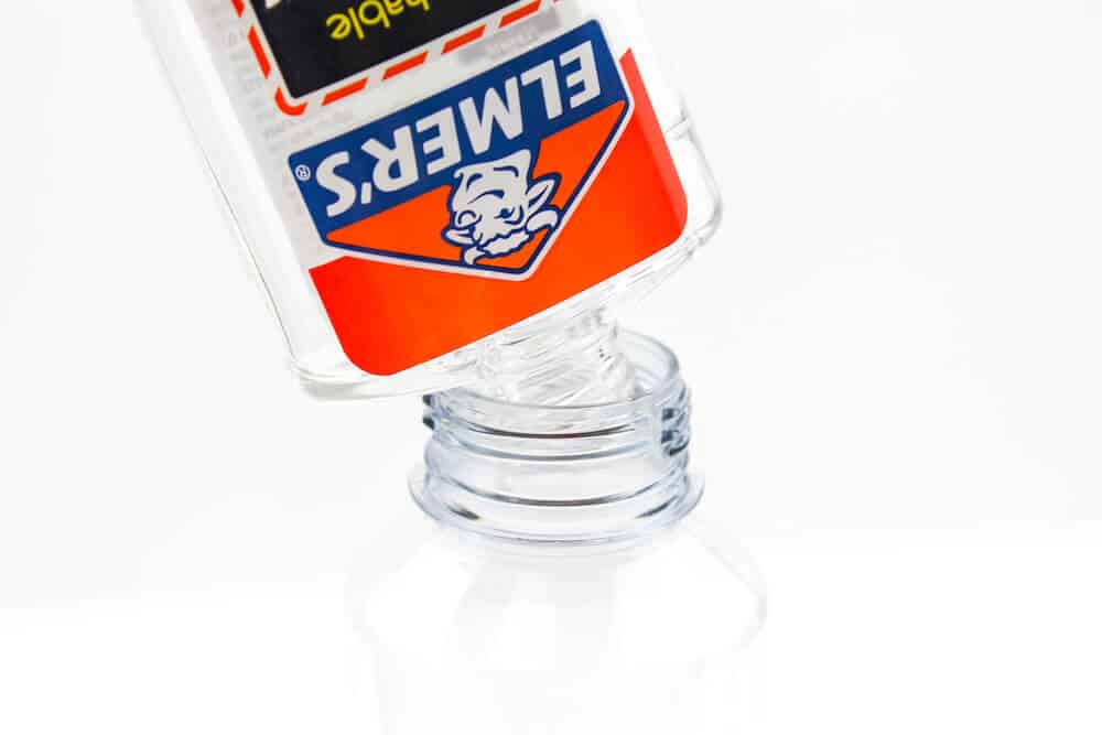 A process photograph showing elmer's glue being poured into a clear plastic bottle as part of making an ocean sensory bottle for children