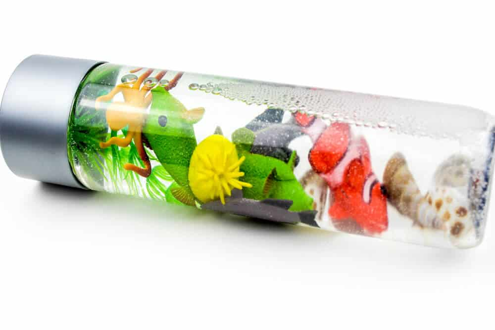 An ocean sensory bottle for children isolated against a white background. Inside the bottle there are a number of colorful plastic fish, plants, and some seashells.