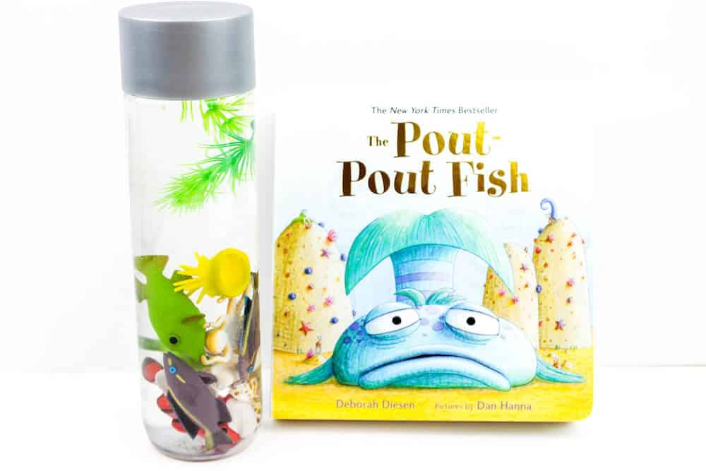 An ocean sensory bottle for children isolated against a white background. Inside the bottle there are a number of colorful plastic fish, plants, and some seashells. The children's book The Pout Pout Fish is pictured beside the ocean sensory bottle.