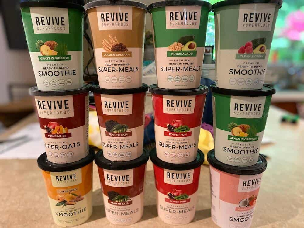 12 Revive Superfoods cups stacked in 4 groups of 3 on a kitchen counter.