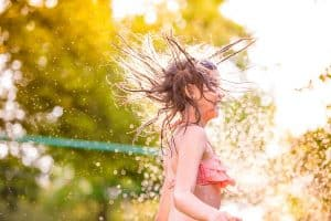 A young girl in a bikini playing outdoors in a sprinkler in summer.