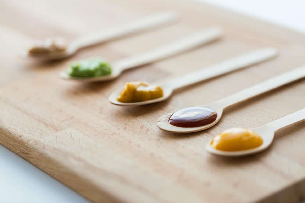 Colorful vegetable or fruit puree on 5 wooden baby spoons. The spoons are lined up side by side on a wooden cutting board.
