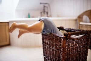 A toddler diving face first into a laundry basket full of clothes