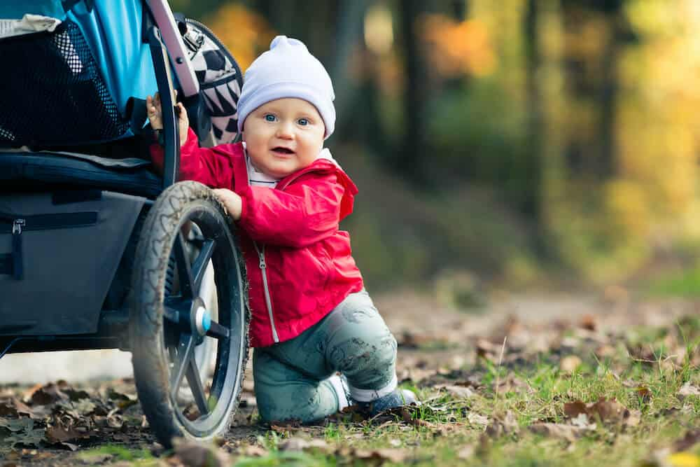 a baby boy playing outside in the autumn near his stroller. The stroller appears to have a stroller organizer attached.