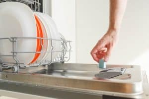 A man's hand puts a dishwasher detergent pack into the dishwasher full of dishes.