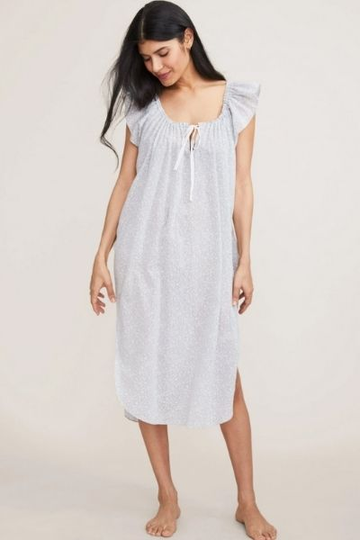A woman models a cotton postpartum pajama gown against an isolated grey background