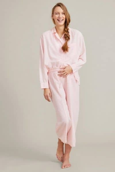 A woman models pink traditional pajamas set for nursing moms against an isolated grey background