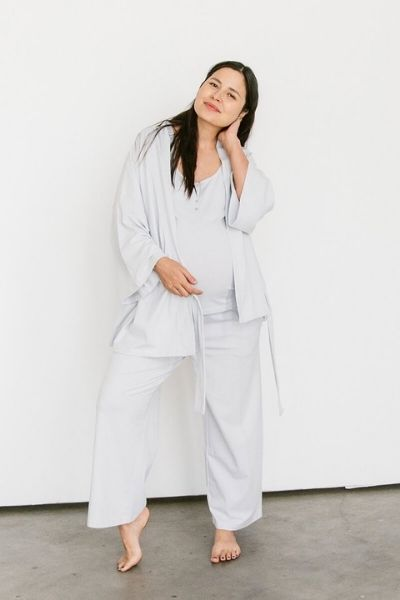 A woman models a 3 piece maternity and postpartum pajamas set of a robe, a tank, and cropped loose pants in light grey