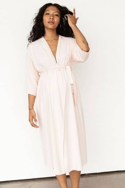 A woman models the Storq labor robe in light pink