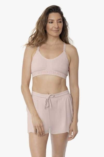 A model wears Kindred Bravely postpartum bamboo shorts and a nursing bra against an isolated white background