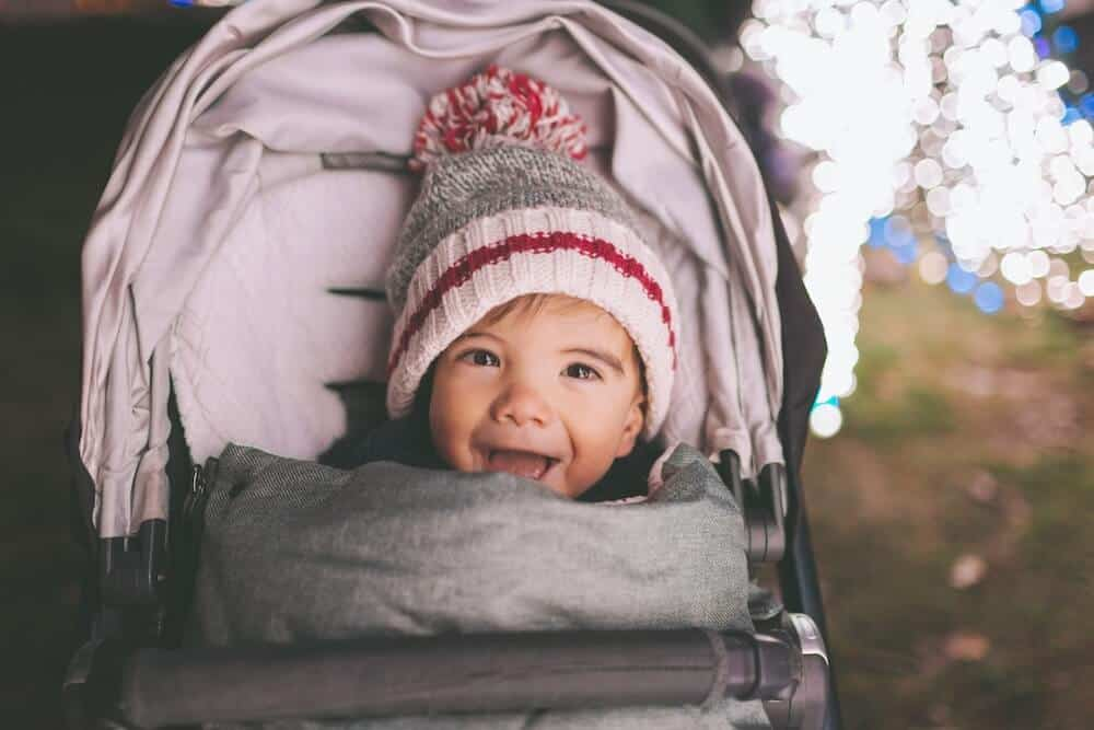 A happy baby bundled up in a stroller footmuff to see Christmas lights
