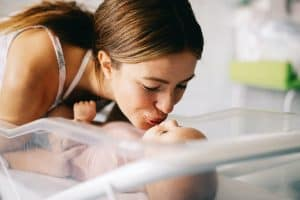 A mother kissing her newborn baby in the hospital after labor.